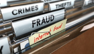 Close up on a file tab with the text fraud plus a note where it is handwritten internet frauds. Blur effect. Concept image for illustration of online scams or cybercrime.